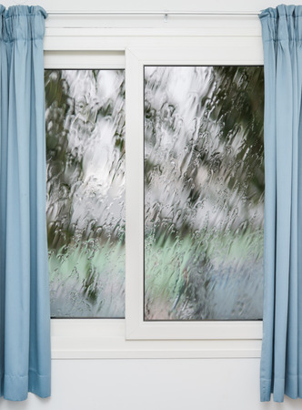 is raining: Closed window with curtains in rainy autumn weather Stock Photo