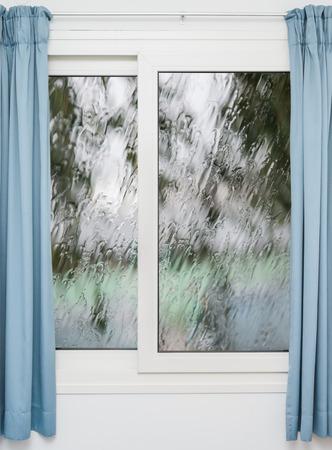 lloviendo: Ventana cerrada con cortinas en tiempo de lluvia de otoño Foto de archivo