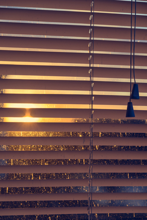 jalousie: closed plastic blinds on the window with the reflection in the glass