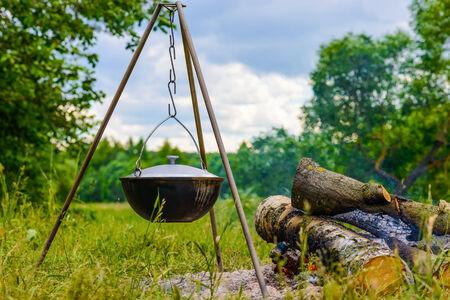 hanging around: hervidor de agua en un tr�pode que cuelga alrededor de una fogata