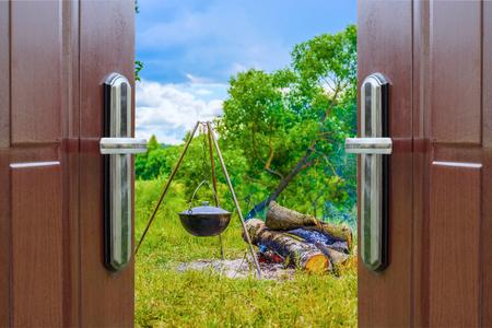 hanging around: hervidor de agua en un tr�pode que cuelga alrededor de una puerta abierta hoguera