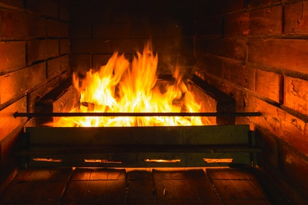 brightly burning flame of fire in the fireplace of brick photo