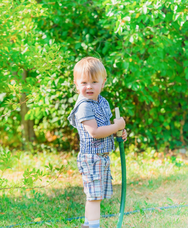 little blond boy pours water from a hose in the garden plant photo