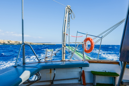 gangway: lifebuoy hanging on a raised gangway of the ship going in the sea Stock Photo