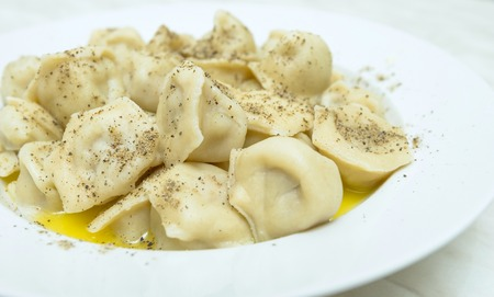 serving of boiled dumplings with pepper on a plate photo