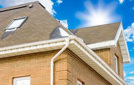 schoorsteen op het dak van het huis tegen de blauwe hemel Stockfoto