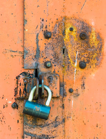 keep gate closed: closed lock of hinged door on an old rusty metal peeled paint Stock Photo