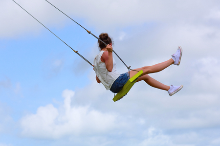 woman sitting on a swing high in the summer day