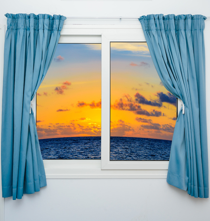 window curtain: beautiful sunset on the sea view from the window with curtains open Stock Photo