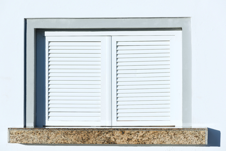 sipario chiuso: closed plastic blinds on the window with the reflection in the glass