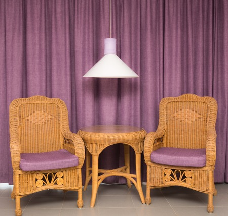 cane sofa: furniture two chairs made of rattan table on a background of curtains and lamps Stock Photo