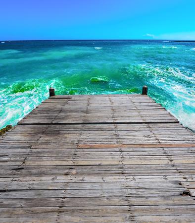 batten: wooden batten bridge juts out into the expanse of the sea Stock Photo