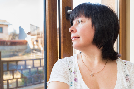 middleaged: Brunette middle-aged woman is looking out the window