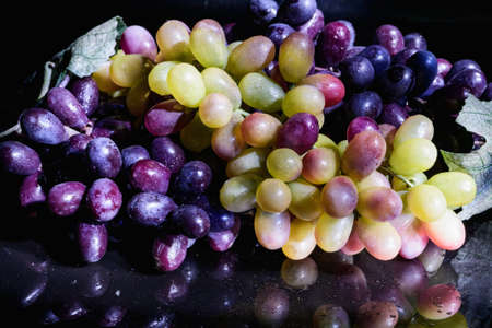 bacca: bouquet of red and white grapes on a glass table