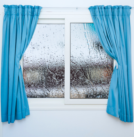 white window: Closed window with curtains in rainy autumn weather Stock Photo