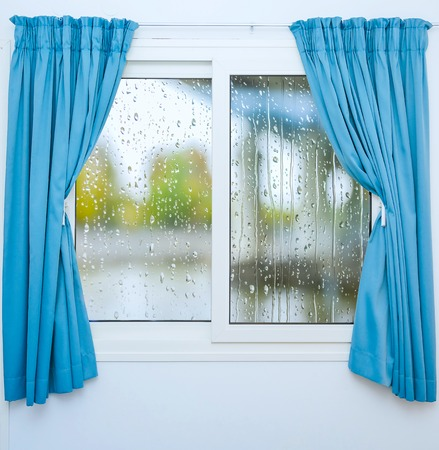 Closed window with curtains in rainy autumn weather Stock Photo