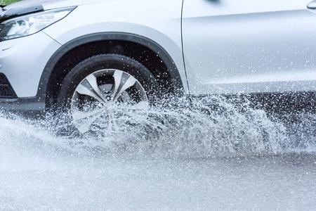 動車雨の大きな水たまり、車輪からの水スプレー