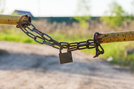 private access: barrier in a field on the lock with a chain lock chain