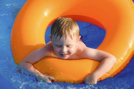little boy swimming: little boy swimming in the pool on an inflatable circle