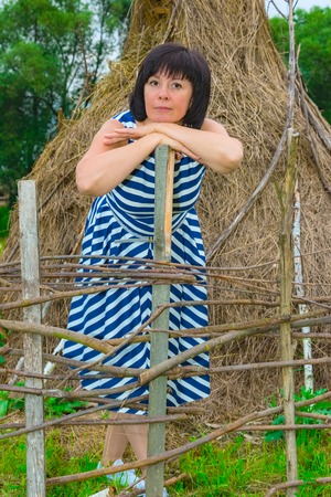 haymow: brunette woman in striped dress standing near a stack of hay countryside