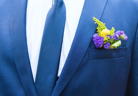 a small bouquet of flowers in his coat pocket festive groom