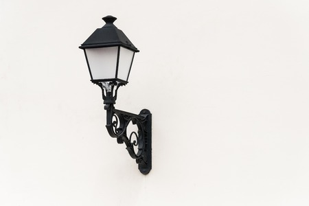 plafond: old lantern forged from metal hanging on the wall Stock Photo