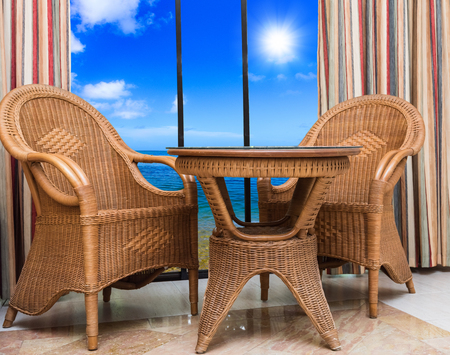 Wicker rattan furniture interior room with a window overlooking the nature Stock Photo