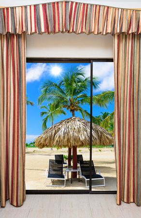 beach window: a large window with a curtain overlooking the beach palm tree