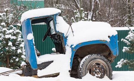 abandoned car: battered old car abandoned covered with snow in winter Stock Photo