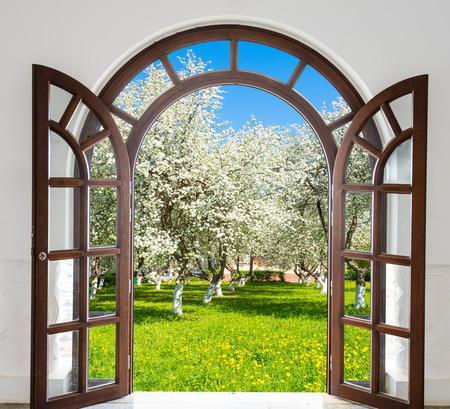 lattice window: Wooden open door arch overlooking the garden trees bloom in spring Stock Photo