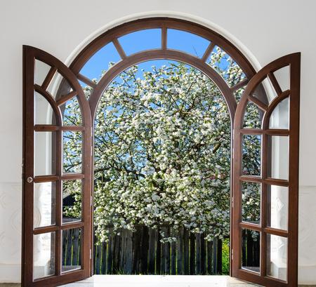 Wooden open door arch overlooking the garden trees bloom in spring Stock Photo
