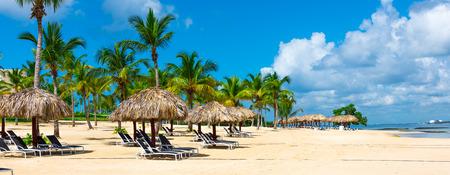 Group deck chairs under an umbrella on a sandy beach sea Foto de archivo