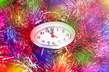 midnight: New Year Clock lie in brightly colored shiny tinsel