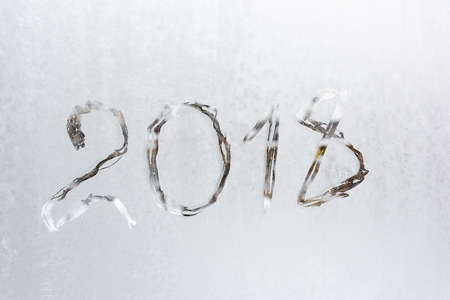 the inscription on the frozen glass covered with frost digit of the year Imagens