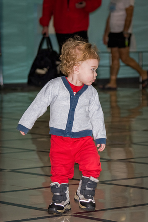 Shaggy little boy in red pants and jacket