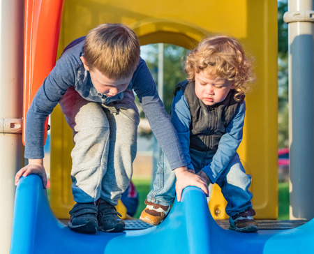 Senior and younger brothers ride the slides on the playground photo