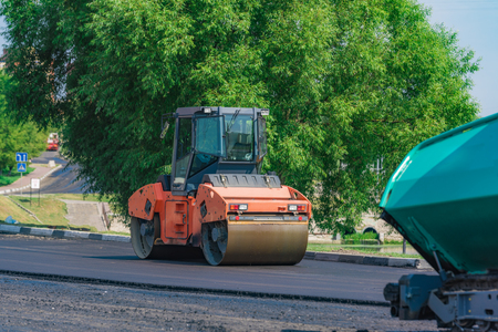Roller machine rolls fresh laid asphalt on the road in the city Stock Photo