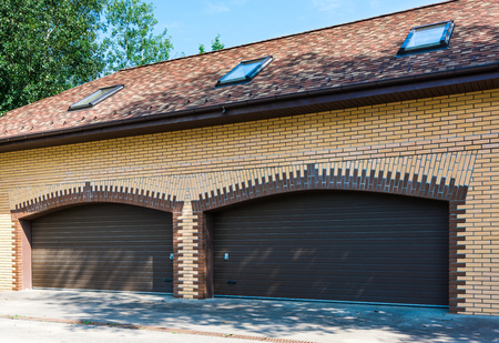 sectional door: brick yellow garage in a private house with a brown gate closed Stock Photo
