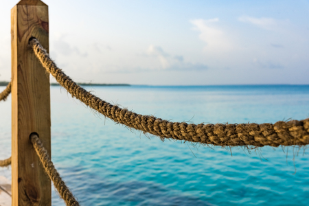pier rope fence leaves in a sea of turquoise color close-up perspective