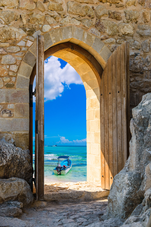 old wooden arch in the fortress with open doors view of the Caribbean Sea Stock Photo
