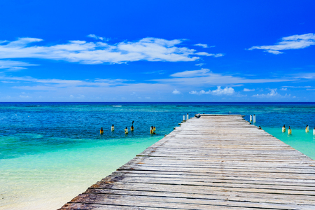 wooden batten bridge juts out into the expanse of the sea Dominican Republic Stock Photo