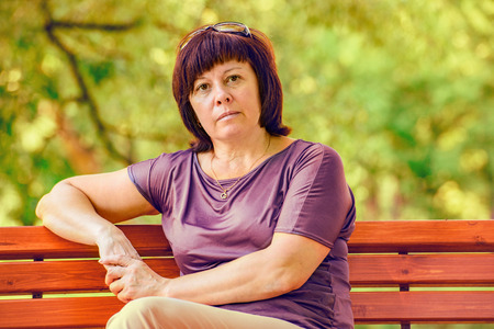 middle-aged brunette woman in a park on vacation Archivio Fotografico