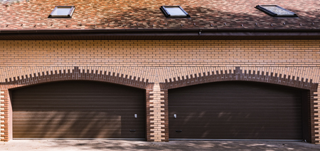 brick yellow garage in a private house with a brown gate closed Stock Photo