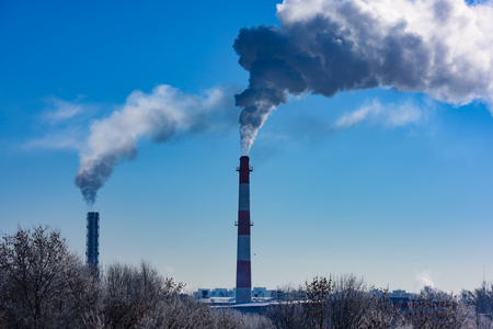 smoke from a chimney factory frosty in the winter against a background of blue sky ecology mud greenhouse effect Stock Photo