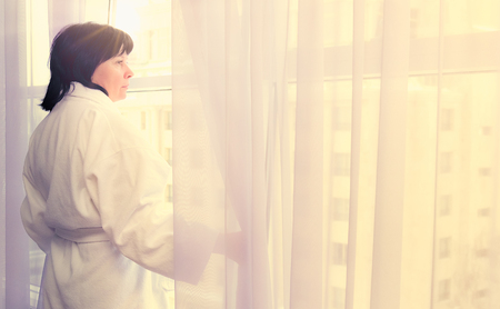 brunette middle-aged woman at the window at dawn wins sunlight 写真素材