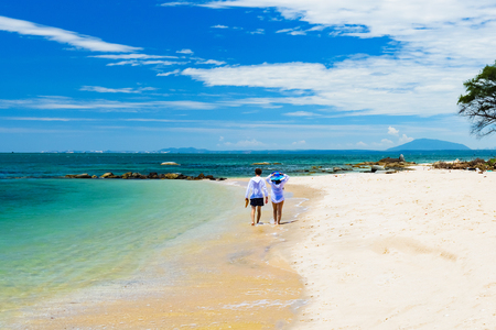 young couple walking along the sand of the tropical coast of the sea for a walk