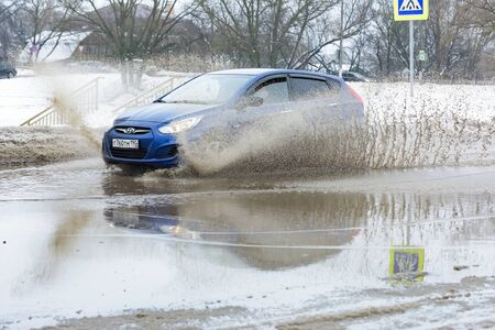 Russia. Moscow. 15 - March 2019. A car drives through a pool of water with splashes. Spring flood in the city. Stock Photo - 137508738