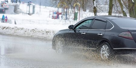 Russia. Moscow. 15 - March 2019. A car drives through a pool of water with splashes. Spring flood in the city. Editorial