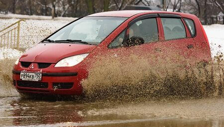 Russia. Moscow. 15 - March 2019. A car drives through a pool of water with splashes. Spring flood in the city. Stock Photo - 137508776