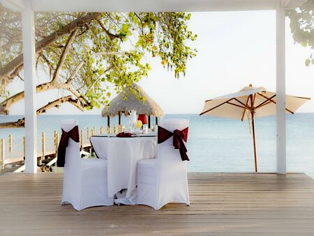 Romantic dining table for honeymooners in a gazebo on the Caribbean